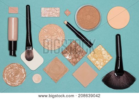 Corrective makeup set, flat lay. Concealer stick, primer, liquid and cream foundation with correcting, bronzing, highlighting, shimmer golden powder, make up brushes and sponges