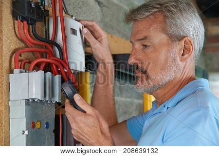 Man Taking Reading From Domestic Electricity Meter