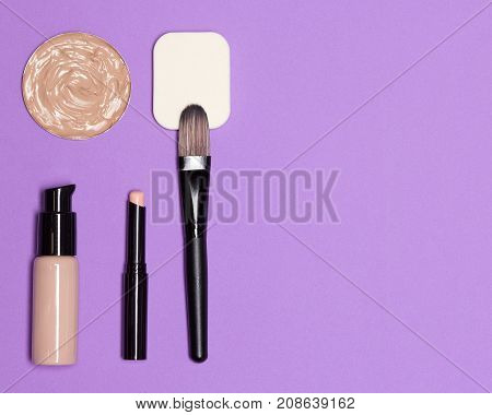 Basic cosmetic products and accessories for corrective makeup: concealer stick, foundation with flat make up brush and sponge, free space for text