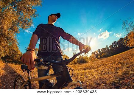 Young Caucasian Athletic Guy On The Sports Bike Staring Into The Distance On An Autumn Background