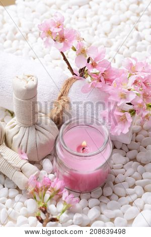 Pink cherry with rolled towel ,candle on pile of white stones