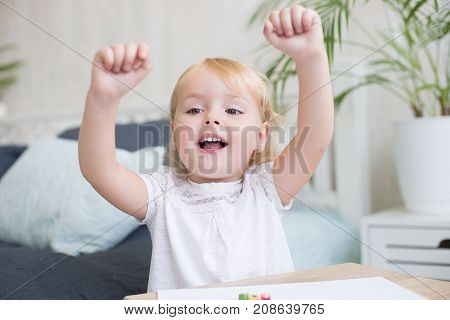 Happy vivacious little blond girl cheering raising her fists in the air with a beaming smile and laughing
