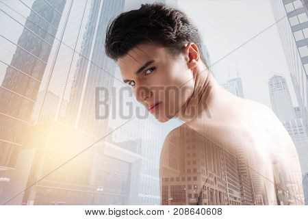 Walking through the city. Close up of talented young model looking at you with coldness while going through the city
