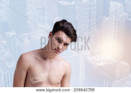 Charming glance. Young naked model looking at you while expressing calmness and standing against urban background