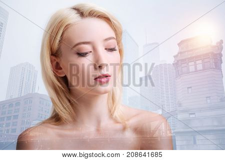 Perfect makeup. Close up of pleasant nude model looking down while standing against city background