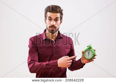 Young businessman is pointing at clock that shows five to twelve time.