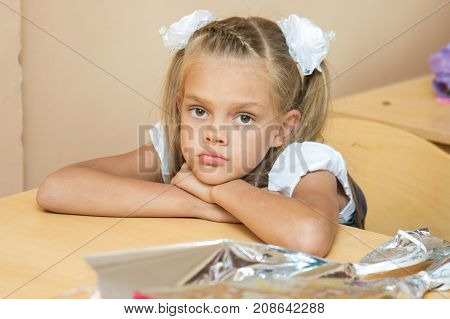 A sad girl at her desk at the lesson of the first of September