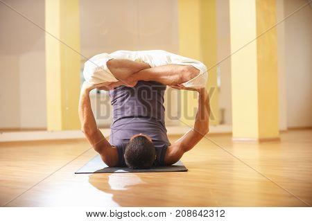 A young strong man doing yoga exercises - Urdhva Padmasana inversion lotus pose in yoga studio.