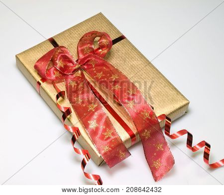 Present wrapped in gold with decorative red bow