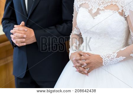 Unrecognizable Bride And Groom In The Church During The Christian Wedding Ceremony. Hands Of Brides