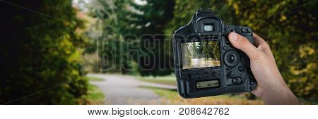 Cropped hand of photographer holding camera  against autumn leaves on road