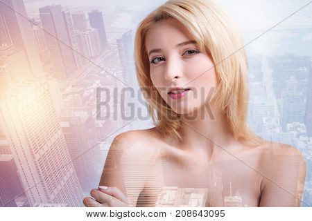 Huge city. Young pretty model expressing satisfaction while standing against pleasant city background