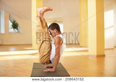 A young strong man doing handstanding yoga exercises - Urdhva Brahmachariasana in yoga studio.