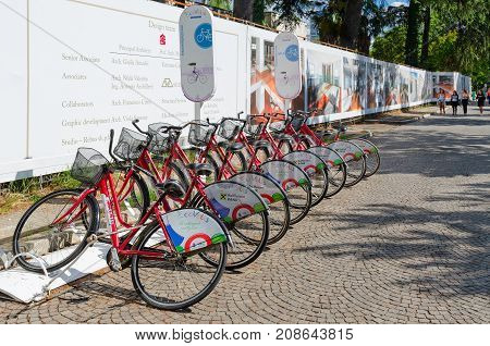 TIRANA ALBANIA - SEPTEMBER 6 2017: Automatic bicycle rental on boulevard of Martyrs point of city program Ecovolis Tirana Albania. Unknown young people are walking down street