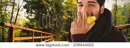 Portrait of man eating pear against bridge with railings leading towards forest