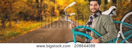 Portrait of smiling man carrying  bicycle against country road along trees in the lush forest