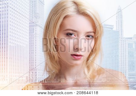 Flawless face. Close up of pretty blonde having peaceful mood while standing against city background