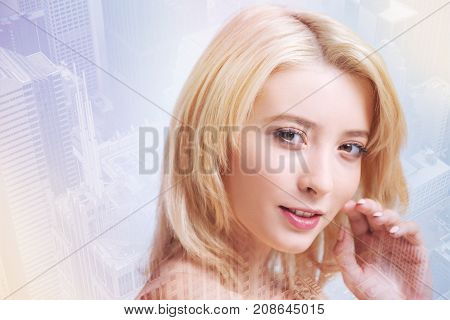 Beauty and youth. Close up of adorable girl looking at you with a smile while touching her face with a hand