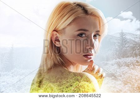 Nature and beauty. Close up of naked model having magnificent expression on her face while touching her chin with a hand