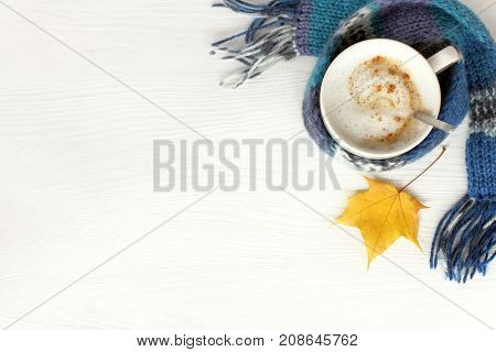 flat lay with mug frothy cappuccino in blue scarf and maple leaf on table top view / warming coffee with autumn