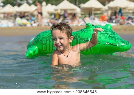 smiling baby boy son in green baseball cap playing in the sea in the day time. Positive human emotions, feelings, joy. Spring and summer holidays.