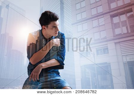 Cold glace. Waist up of fashionable teenager sitting against city background while looking away