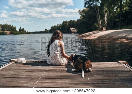 Relaxing with her best friend. Rear view of little girl and her dog sitting near the lake while spending time outdoors