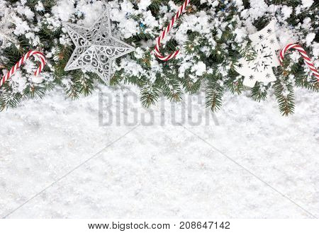 Christmas background with Christmas fir tree border decorated with candy canes ornaments and snow flakes on a thick layer of iridescent snow.