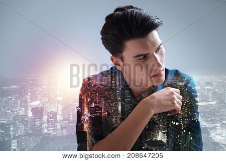 Lonely evening. Good looking teenager with a stylish haircut standing against city background while averting his eyes