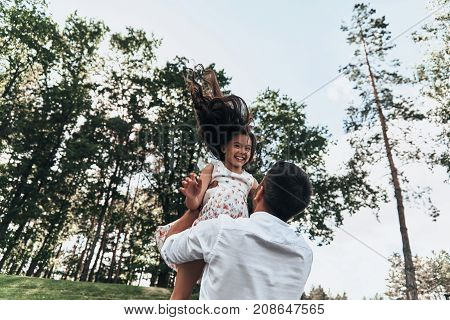 Dad is her best friend. Young loving father carrying his smiling daughter while spending free time outdoors