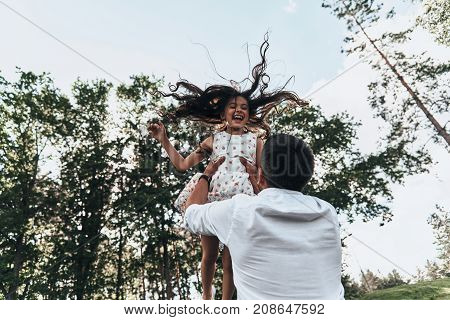 She is his princess. Young loving father carrying his smiling daughter while spending free time outdoors
