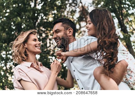 Enjoying every moment together. Happy young family of three smiling while spending free time outdoors
