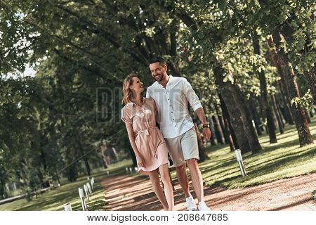They belong together. Beautiful young couple bonding and smiling while walking in the park