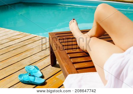 Relaxing woman near luxury swimming pool sunbath summer day at the beach resort in the hotel. Concept Summer Rest.