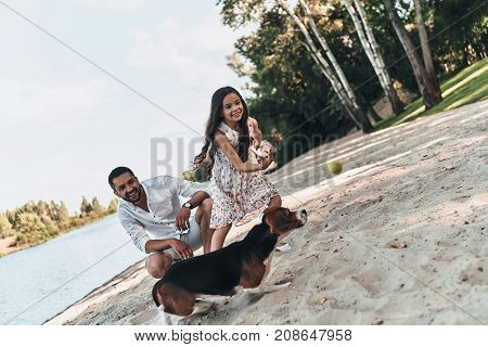 Enjoying great sunny day. Happy young family playing with dog and smiling while spending time on the lake shore