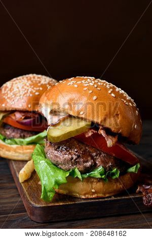 Tasty hamburger with beef bacon tomato lettuce and marinated cucumber on wooden board