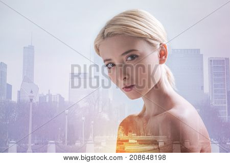 New photo session. Close up of beautiful model expressing optimism while standing against city background