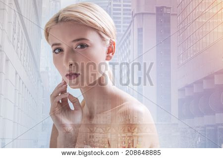 Time for contemplations. Close up of naked model being thoughtful while touching her face against city background