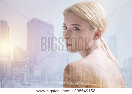 Being calm. Charming blonde girl looking away while standing against city background