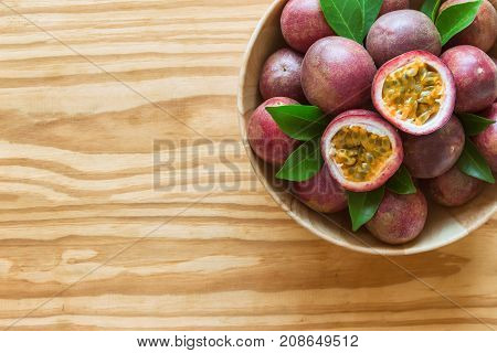 Fresh passion fruit in wood bowl on wood table in top view flat lay with copy space for background or wallpaper. Ripe passion fruit so sweet and sour. Passion fruit is tropical fruit. Passion fruit background concept.