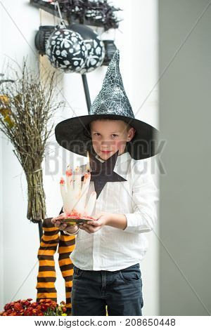 Halloween Holiday and celebration. Halloween child with cute face. Party and traditional costume. Kid with bloody candle. Small boy in spider web witch hat at striped socks.