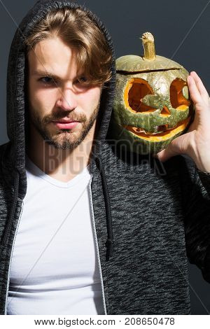 young handsome bearded sexy man with stylish hair in white shirt and jacket in studio on grey wall background holds orange golden halloween traditional pumpkin with scary face copy space