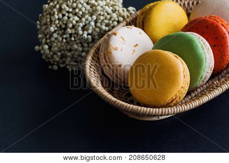 Colorful French macaron or Italian macaron stack on basket. Homemade delicious macaron on granite table with copy space for background or wallpaper. French dessert for served with tea or coffee. Pastel color macarons ready to served.