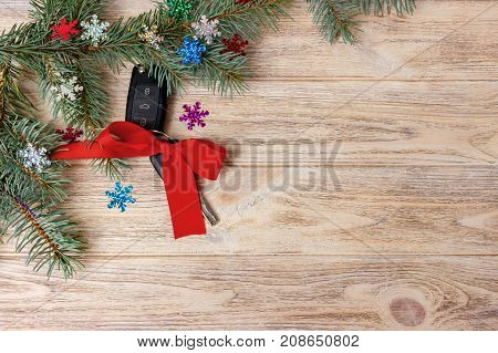 Car key with colorful bow on wooden background.