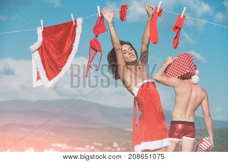 Christmas man and woman family. New year guy with muscular body on blue sky. Laundry and dry cleaning. Couple in love of man and girl hanging clothes for drying. Xmas red costume on rope with pin.