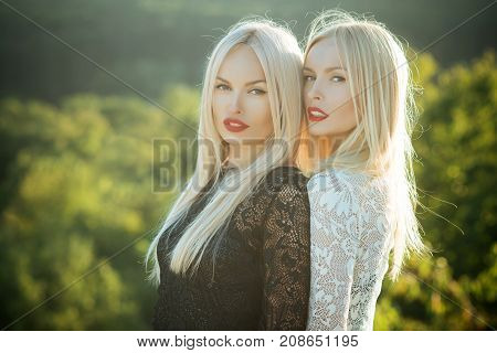 Two Women With Red Lips And Long Blond Hair