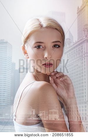 Pure skin. Close up of pleasant model keeping her hand under the chin while standing in urban surrounding