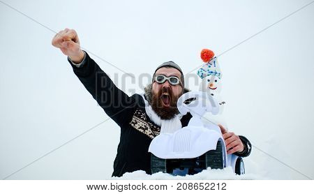 Hipster in pilot hat and glasses on white sky. Excited man with raised fist hand. Snowman driving toy car on snowy landscape. Solidarity and support concept. Christmas and new year holiday celebration