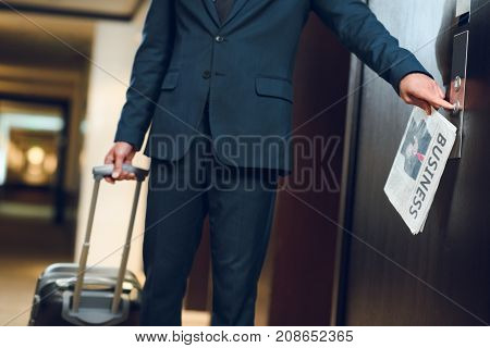 businessman in hotel corridor with a suitcase and newspaper pushing elevator button