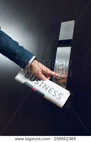 Cropped shot of businessman in hotel corridor with a newspaper in his hand pushing elevator button